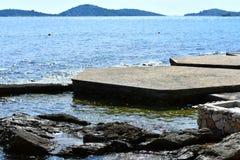 与岩石海岸线和sparkiling的海水的蓝色海景 免版税库存照片