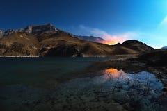 与岩石的反射的一个美好的夜风景在有灼烧的山的一个山湖在背景中 库存照片