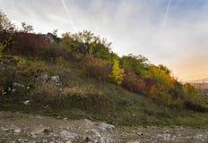 与岩石的山在秋天黄色和红颜色 秋天场面 免版税库存照片