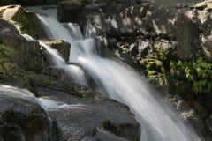 与岩石的流动的瀑布 免版税库存照片
