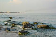与岩石的海岸,在与大厦的天际海滩 库存照片