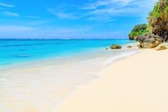 与岩石的热带海滩在一个完善的夏日 免版税库存照片