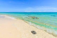 与岩石的热带海滩在一个完善的夏日 库存照片