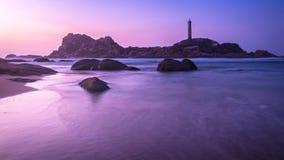 与岩石的自然海景在海滩、柔滑的水、海岛和灯塔在日出前Paranomic背景的 库存照片
