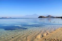 与岩石的透明海洋在松巴哇岛海岛的水和山靠岸,印度尼西亚 免版税库存图片