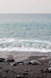 与岩石的黑沙子海滩 库存图片