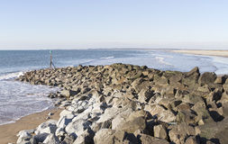 与岩石防堤的沿海在砂石Dinlle 免版税库存图片