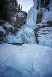 与峡谷冰冷的墙壁和冰大片断的长的结冰的瀑布在前面,约翰斯顿峡谷,班夫国家公园,加拿大的 库存照片