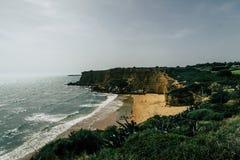 与峭壁的美好的西班牙海岸线:海滩,海,与白色冠的波浪在日落期间 免版税库存图片