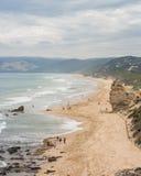 与峭壁的长的沙滩和轻拍波浪 免版税图库摄影
