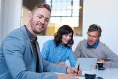 与工作在背景中的同事的微笑的年轻商人 免版税库存图片