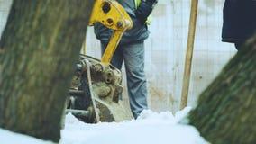 与工作者一起的挖掘机在冬天做修理工作 影视素材