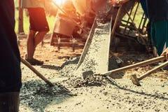 与工作者的倾吐的混凝土混合修造的路的水泥在骗局 免版税库存照片