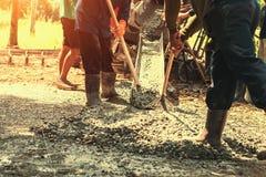 与工作者的倾吐的混凝土混合修造的路的水泥在骗局 图库摄影