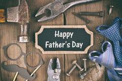 与工具、礼物和领带框架的愉快的父亲节黑板标记在木头 免版税库存照片