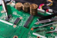 与工具和硬币,螺丝刀,焊铁,刀子,关闭的PCB绿色 免版税图库摄影
