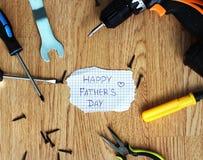 与工具的愉快的父亲节在土气木背景 免版税图库摄影