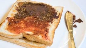与巧克力传播的鲜美面包多士和草莓酱 库存图片