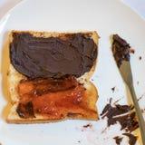 与巧克力传播的鲜美面包多士和草莓酱 库存照片