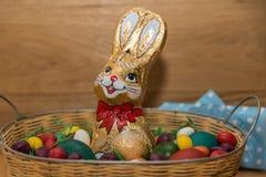 与巧克力兔宝宝和五颜六色的鸡蛋的复活节篮子 免版税库存图片