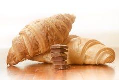 与巧克力块的两个被烘烤的新月形面包 免版税库存照片