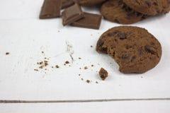 与巧克力块的巧克力饼干在白色木头 图库摄影