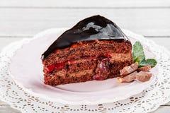 与巧克力奶油和结冰的黑暗的巧克力蛋糕,用在板材的樱桃,在轻的木背景 免版税库存图片