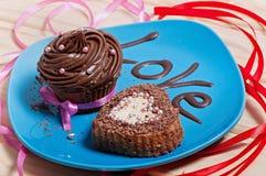 与巧克力奶油的巧克力杯形蛋糕和以心脏的形式巧克力杯形蛋糕在有题字的一块蓝色板材爱 免版税库存图片