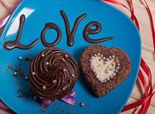 与巧克力奶油的巧克力杯形蛋糕和以心脏的形式巧克力杯形蛋糕在有题字的一块蓝色板材爱 免版税库存照片