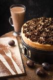 与巧克力奶油的经典乳酪蛋糕在闪烁金子 库存照片