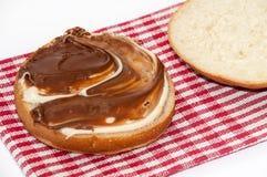 与巧克力奶油的面包在厨房用桌布料 免版税库存图片