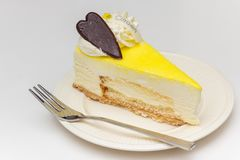 与巧克力心脏的柠檬乳酪蛋糕在一块白色板材 免版税库存照片