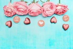 与巧克力心脏的浅粉红色的玫瑰边界和爱消息在绿松石背景,顶视图签字 免版税库存照片