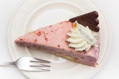 与巧克力心脏的草莓乳酪蛋糕在一块白色板材 免版税图库摄影