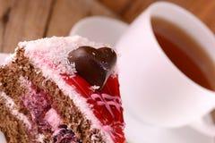 与巧克力心脏的蛋糕在木背景 免版税库存照片