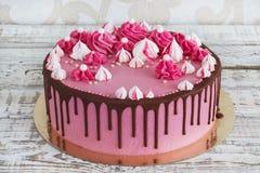 与巧克力污点的桃红色奶油色蛋糕蛋白甜饼在白色木背景的 免版税库存照片