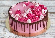 与巧克力污点的桃红色奶油色蛋糕蛋白甜饼在白色木背景的 图库摄影