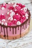 与巧克力污点的桃红色奶油色蛋糕蛋白甜饼在白色木背景的 免版税图库摄影