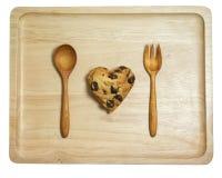 与巧克力片的心脏曲奇饼在被隔绝的木盘子 免版税库存图片