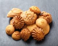 与巧克力片,在石板岩背景的燕麦粥葡萄干的被分类的曲奇饼在木背景关闭 烘烤自创 库存图片