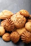 与巧克力片,在石板岩背景的燕麦粥葡萄干的被分类的曲奇饼在木背景关闭 烘烤自创 免版税库存照片