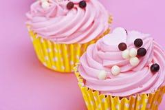 与巧克力球的两甜点杯形蛋糕在一桃红色backgr 免版税图库摄影