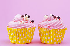 与巧克力球的两甜点杯形蛋糕在一桃红色backgr 库存图片