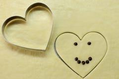 与巧克力眼睛的微笑的与烹调形状心脏顶视图的心脏和微笑 浪漫概念 情人节符号 免版税库存照片