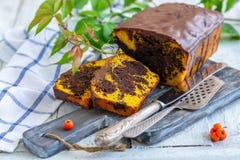 与巧克力结冰的被切的大理石花纹蛋糕 免版税图库摄影