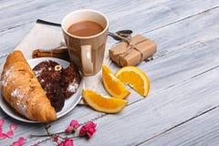 与巧克力蛋糕的一个新月形面包和在灰色木背景的一个桔子,在它旁边是被洒的桃红色瓣,自由 库存图片