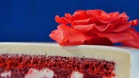 与巧克力装饰品和红色小杏仁饼的白蛋糕在深蓝背景上升了 用可食的英国兰开斯特家族族徽装饰的蛋糕 免版税库存照片
