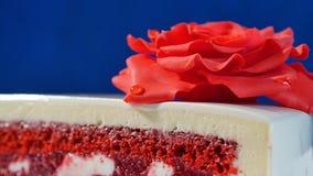 与巧克力装饰品和红色小杏仁饼的白蛋糕在深蓝背景上升了 用可食的英国兰开斯特家族族徽装饰的蛋糕 免版税库存图片