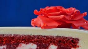 与巧克力装饰品和红色小杏仁饼的白蛋糕在深蓝背景上升了 用可食的英国兰开斯特家族族徽装饰的蛋糕 库存图片