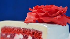 与巧克力装饰品和红色小杏仁饼的白蛋糕在深蓝背景上升了 用可食的英国兰开斯特家族族徽装饰的蛋糕 库存照片
